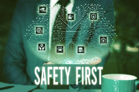 Handwriting text Safety First. Conceptual photo used to say that the most important thing is to be safe Male human wear formal work suit presenting presentation using smart device