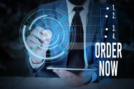 Writing note showing Order Now. Business concept for the activity of asking for goods or services from a company Male wear formal suit presenting presentation smart device Stock Photo