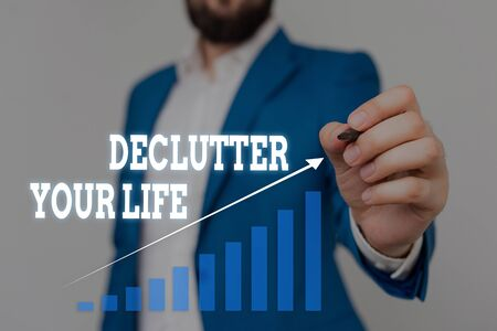 Text sign showing Declutter Your Life. Business photo showcasing To eliminate extraneous things or information in life Male human wear formal work suit presenting presentation using smart device