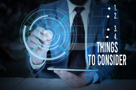 Writing note showing Things To Consider. Business concept for think about carefully especially in making decisions Male wear formal suit presenting presentation smart device