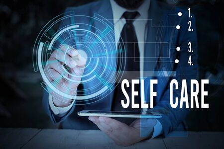 Writing note showing Self Care. Business concept for the practice of taking action to improve one s is own health Male wear formal suit presenting presentation smart device Stockfoto