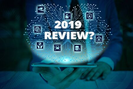 Writing note showing 2019 Review Question. Business concept for remembering past year events main actions or good shows Male wear formal work suit presenting presentation smart device