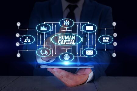 Text sign showing Huanalysis Capital. Business photo text Intangible Collective Resources Competence Capital Education Male human wear formal work suit presenting presentation using smart device Banco de Imagens