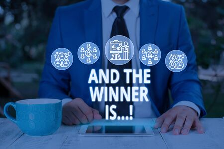Text sign showing And The Winner Is. Business photo text announcing who got first place at competition or exam Male human wear formal work suit presenting presentation using smart device Archivio Fotografico - 129713787
