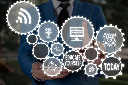 Text sign showing Educate Yourself. Business photo text prepare oneself or someone in a particular area or subject Male human wear formal work suit presenting presentation using smart device Stock Photo