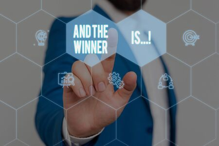 Text sign showing And The Winner Is. Business photo text announcing who got first place at competition or exam Male human wear formal work suit presenting presentation using smart device Archivio Fotografico - 129720622