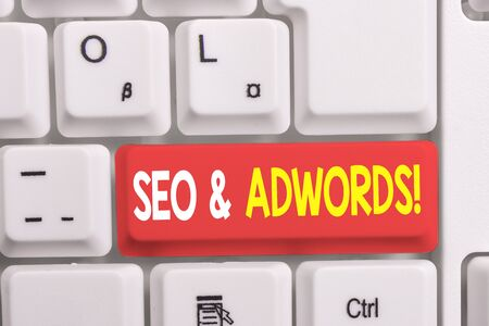 Writing note showing Seo And Adwords. Business concept for they are main tools components of Search Engine Marketing White pc keyboard with note paper above the white background