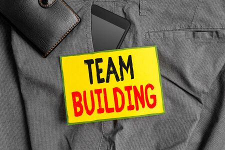 Conceptual hand writing showing Team Building. Concept meaning various types of activities used to enhance social relations Smartphone device inside trousers front pocket with wallet Stockfoto