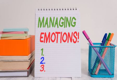 Text sign showing Managing Emotions. Business photo text ability be open to feelings and modulate them in oneself Pens metal holder stacked note pads books square box spiral wooden table 写真素材
