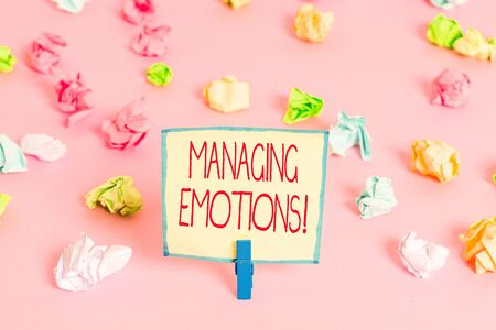 Text sign showing Managing Emotions. Business photo text ability be open to feelings and modulate them in oneself Colored crumpled papers empty reminder pink floor background clothespin 写真素材