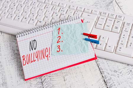 Text sign showing No Bullying. Business photo showcasing stop aggressive behavior among children power imbalance notebook paper reminder clothespin pinned sheet white keyboard light wooden Archivio Fotografico
