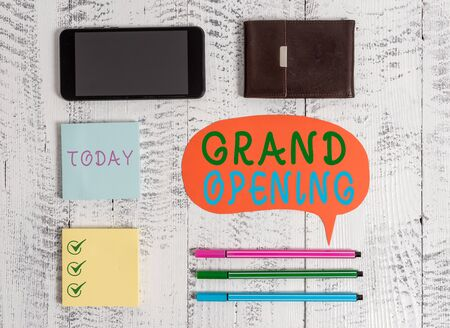 Word writing text Grand Opening. Business photo showcasing Ribbon Cutting New Business First Official Day Launching Smartphone pens blank speech bubble sticky notes wallet wooden background Imagens