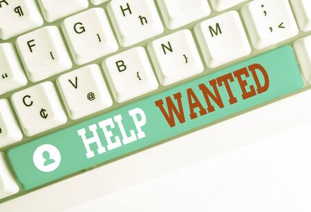 Word writing text Help Wanted. Business photo showcasing An ad in the paper an employer places to find a new employee White pc keyboard with empty note paper above white background key copy space 스톡 콘텐츠