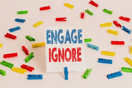 Text sign showing Engage Ignore. Business photo showcasing Silent Treatment Manipulative Punishment Sulking Shunning Colored clothespin papers empty reminder white floor background office