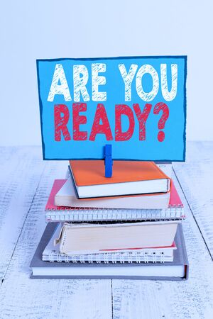 Writing note showing Are You Ready Question. Business concept for used telling someone start something when feel prepared pile stacked books notebook pin color reminder white wooden