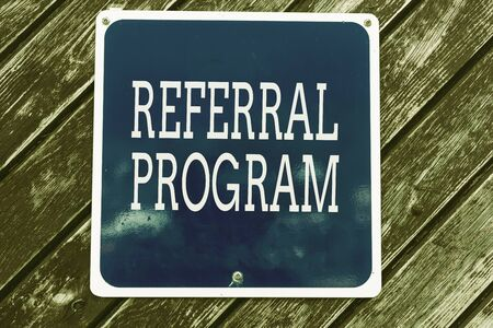 Handwriting text writing Referral Program. Conceptual photo employees are rewarded for introducing suitable recruits Empty blue board with copy space above wooden background