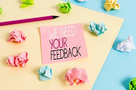 Writing note showing We Need Your Feedback. Business concept for criticism given to say can be done improvement Colored crumpled papers empty reminder blue yellow clothespin