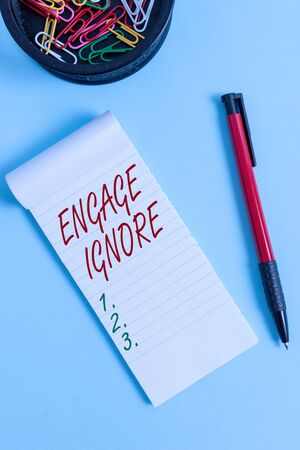 Writing note showing Engage Ignore. Business concept for Silent Treatment Manipulative Punishment Sulking Shunning Notebook and stationary with mouse above pastel backdrop Фото со стока - 129834909