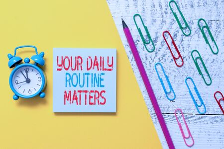 Handwriting text Your Daily Routine Matters. Conceptual photo practice of regularly doing things in fixed order Notepad marker pen colored paper sheet clips alarm clock wooden background Imagens