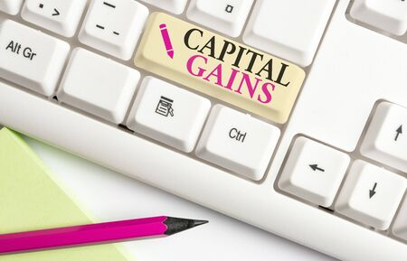 Handwriting text writing Capital Gains. Conceptual photo Bonds Shares Stocks Profit Income Tax Investment Funds White pc keyboard with empty note paper above white background key copy space
