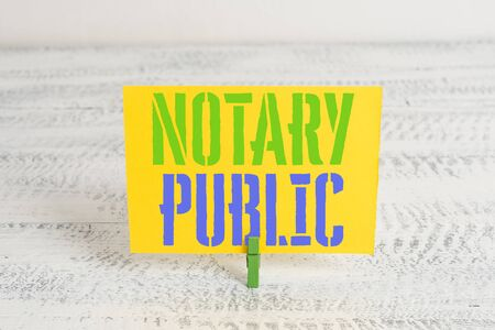 Text sign showing Notary Public. Business photo showcasing Legality Documentation Authorization Certification Contract Green clothespin white wood background colored paper reminder office supply 스톡 콘텐츠