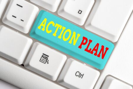 Text sign showing Action Plan. Business photo showcasing detailed plan outlining actions needed to reach goals or vision White pc keyboard with empty note paper above white background key copy space Фото со стока