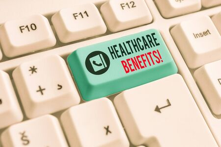 Writing note showing Healthcare Benefits. Business concept for monthly fair market valueprovided to Employee dependents White pc keyboard with note paper above the white background 写真素材 - 129835512