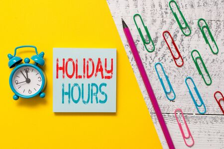 Handwriting text Holiday Hours. Conceptual photo employee receives twice their normal pay for all hours Notepad marker pen colored paper sheet clips alarm clock wooden background Reklamní fotografie