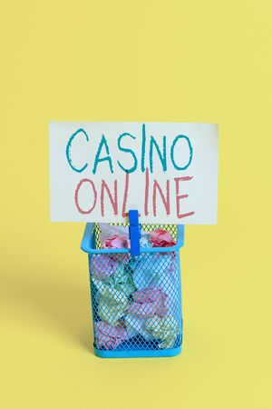 Handwriting text Casino Online. Conceptual photo Computer Poker Game Gamble Royal Bet Lotto High Stakes Trash bin crumpled paper clothespin empty reminder office supplies yellow Stockfoto