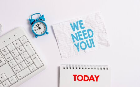 Text sign showing We Need You. Business photo showcasing asking someone to work together for certain job or target Blank paper with copy space on the table with clock and pc keyboard