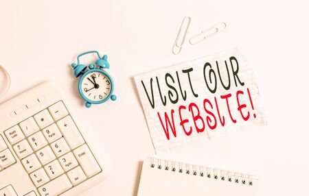 Writing note showing Visit Our Website. Business concept for visitor who arrives at web site and proceeds to browse Blank paper with copy space on the table with clock and pc keyboard Фото со стока