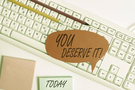 Word writing text You Deserve It. Business photo showcasing should have it because of their qualities or actions Empty copy space red note paper bubble above pc keyboard for text message