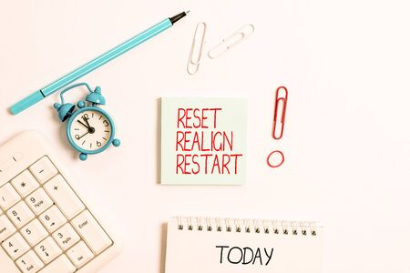 Writing note showing Reset Realign Restart. Business concept for Life audit will help you put things in perspectives Copy space on empty note paper with clock and pencil on the table Stock Photo