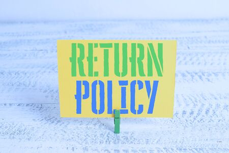 Text sign showing Return Policy. Business photo showcasing Tax Reimbursement Retail Terms and Conditions on Purchase Green clothespin white wood background colored paper reminder office supply Stock Photo