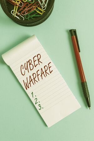 Writing note showing Cyber Warfare. Business concept for Virtual War Hackers System Attacks Digital Thief Stalker Notebook and stationary with mouse above pastel backdrop