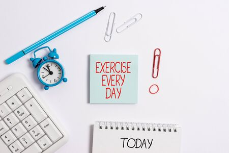 Writing note showing Exercise Every Day. Business concept for move body energetically in order to get fit and healthy Copy space on empty note paper with clock and pencil on the table