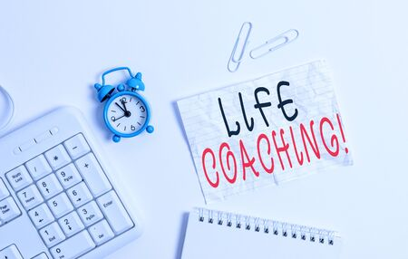 Writing note showing Life Coaching. Business concept for demonstrating employed to help showing attain their goals in career Blank paper with copy space on the table with clock and pc keyboard Stockfoto