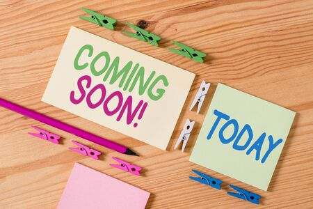 Handwriting text Coming Soon. Conceptual photo event or action that will happen after really short time Colored clothespin papers empty reminder wooden floor background office