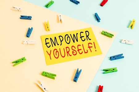 Text sign showing Empower Yourself. Business photo text taking control of our life setting goals and making choices Colored clothespin paper empty reminder yellow blue floor background office Stock Photo