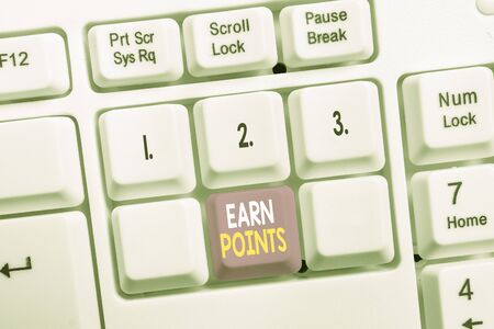 Conceptual hand writing showing Earn Points. Concept meaning getting praise or approval for something you have done White pc keyboard with note paper above the white background Stock Photo