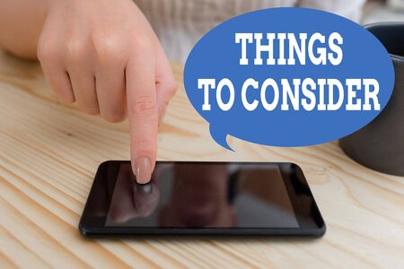 Text sign showing Things To Consider. Business photo text think about carefully especially in making decisions woman using smartphone office supplies technological devices inside home Stok Fotoğraf - 129680843