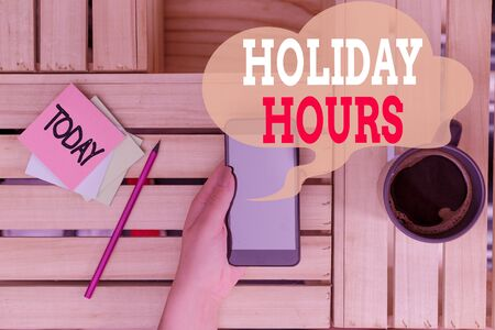 Text sign showing Holiday Hours. Business photo text employee receives twice their normal pay for all hours woman computer smartphone drink mug office supplies technological devices Banco de Imagens - 130128445