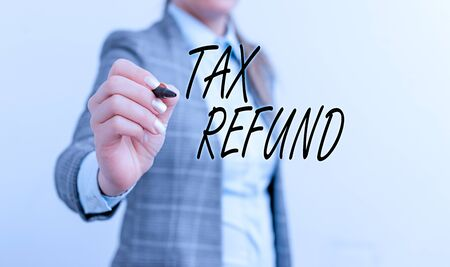 Conceptual hand writing showing Tax Refund. Concept meaning refund on tax when the tax liability is less than the tax paid Business woman pointing in empty space with pen