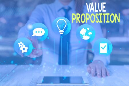 Conceptual hand writing showing Value Proposition. Concept meaning feature intended to make a company or product attractive Female human wear formal work suit presenting smart device Banco de Imagens