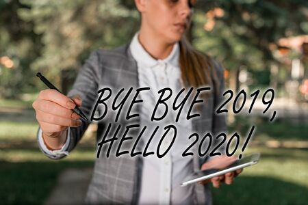 Text sign showing Bye Bye 2019 Hello 2020. Business photo text saying goodbye to last year and welcoming another good one Outdoor background with business woman holding lap top and pen