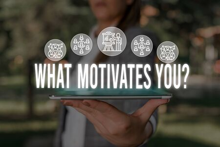 Handwriting text What Motivates Youquestion. Conceptual photo know reasons why you want to wake up each morning Woman wear formal work suit presenting presentation using smart device Zdjęcie Seryjne