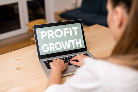 Conceptual hand writing showing Profit Growth. Concept meaning Objectives Interrelation of Overall Sales Market Shares woman with laptop smartphone and office supplies technology Banco de Imagens