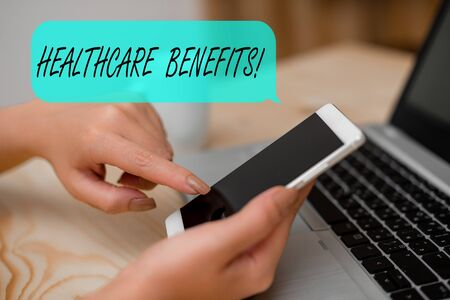 Conceptual hand writing showing Healthcare Benefits. Concept meaning monthly fair market valueprovided to Employee dependents woman with laptop smartphone and office supplies technology