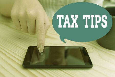 Text sign showing Tax Tips. Business photo text compulsory contribution to state revenue levied by government woman using smartphone office supplies technological devices inside home