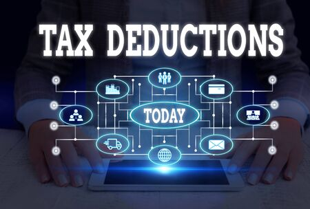 Writing note showing Tax Deductions. Business concept for an amount or cost that subtracted from someone s is income Woman wear formal work suit presenting presentation using smart device